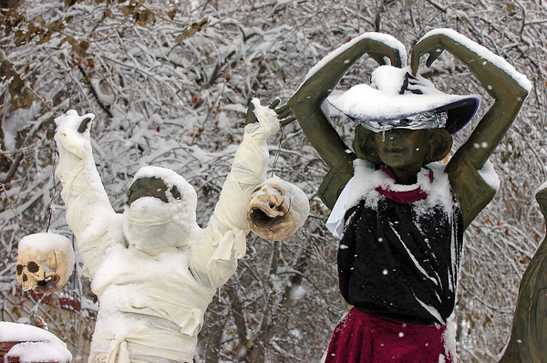 Figures on a Jane DeDecker sculpture dressed as a witch and a mummy are covered in snow on the corner of Eighth Street and Taft Avenue Wednesday in Loveland.