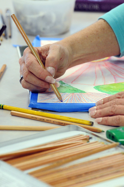 Jen Thompson of Loveland paints hibiscus flowers with watercolor pencils during a painting class at AMES Community College in Loveland.