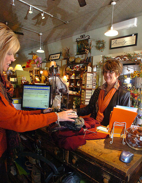 Judy Sheets, left, clothing manager at Almosta Mercantile, helps customer Bobbie Beyersdorf check out with some clothing purchases Friday afternoon at the boutique in downtown Loveland.