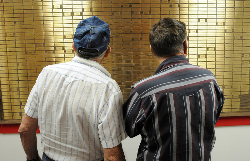 Retired Loveland Firefighters Walt Ballinger, left and Larry Halsey look at the board that holds all of the names of firefighters since 1911 on Thursday as they and other volunteers and former retired firefighters get the new Firefighter Exhibit ready for opening day at the Loveland Museum/Gallery.