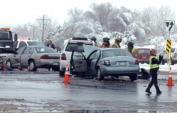 Loveland Police direct traffic at the intersection of 57th Street and Garfield Avenue in Loveland as Loveland Fire and Rescue crews work the scene of a three car accident there Thursday morning.