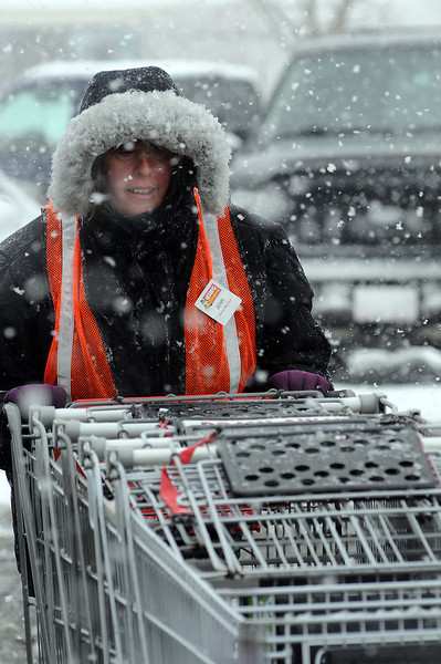 King Soopers employee Jenn Brooks collects carts in the parking lot of the store on Eagle Drive during a snow storm on Wednesday afternoon.