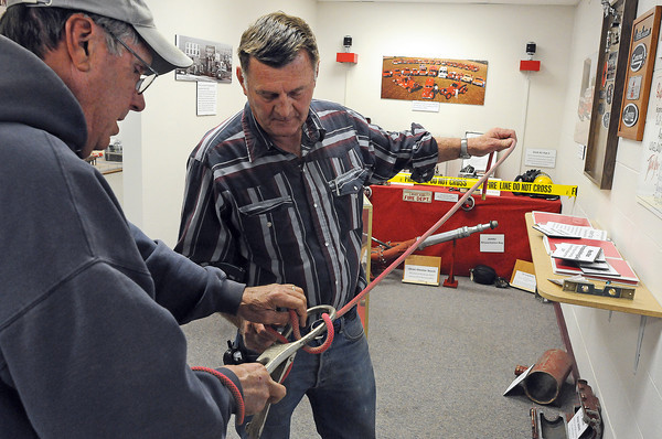 Retired Loveland Firefighters Larry Halsey, right, and Fran Lyons attempt to figure out how a belay device works as they get ready for opening day of the new firefighting exhibit at the Loveland Museum/Gallery.