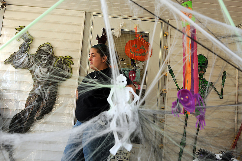 Emily Rock stands on the porch of her friend Andrea Yoder's grandmother, Nola Bracy on Thursday. A trio of night owls, Rock, her sister, Liz, and Yoder, decorated the house for Bracy who is battling cancer.