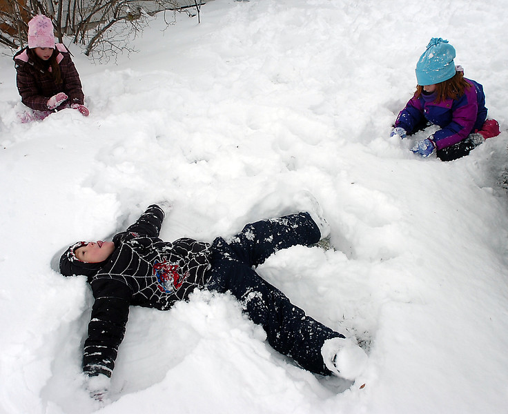 Brandon Reid, 6, makes a snow angel in the deep snow as his sister Lexi Reid, 8, left, and friend Cassie Fanning, 8, right, also play in the snow in the front yard of Cassie's houe on the 1100 block of West Sixth Street in Loveland on Thursday.