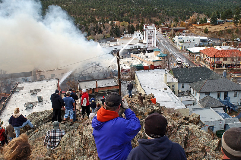 Crowds gather atop a hill on the north side of town to watch firefighters battle a blaze that engulfs the Park Theatre Mall on Monday in Estes Park, Colo. No one was in the structure during the blaze which started after 6 a.m., well before the mall opened.<br /> <br /> AP Photo/Loveland Reporter-Herald, Chris Stark