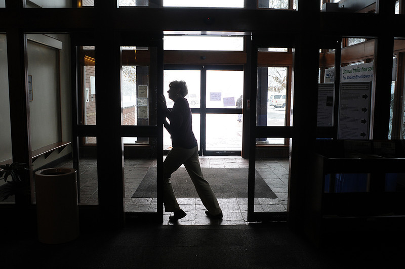 Loveland Public Library librarian Jackie Kietzmann forces open a lobby door on Wednesday following a power outage from the snow storm.