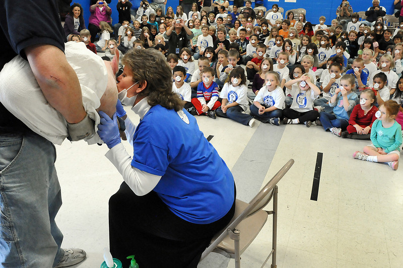 B.F. Kitchen Elementary principal Kandi Smith kisses a pig as the school's students watch on Friday in the lunchroom of the school. The students raised over $6,100 for walking a total of 1,692 laps around the soccer field, an equivalent of 282 miles. Thompson School District grounds operator Seth Woolridge, left, provided the pig from his family's hog farm.<br /> <br /> <br /> Tavian Day, 5, <br /> <br /> Ellizabeth Wheeler, 5,