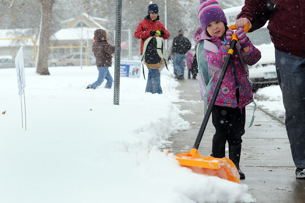 Danika Eisentraut, 5, shovels the snow at Garfield Elementary with the help of her mother, Ginger Eisentraut on Wednesday after school let out. Thompson School District schools were open during the storm and released early as usual. Afternoon conferences did not happen due to the storm.