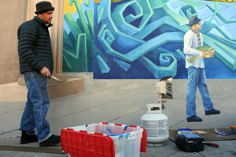 "Muralist Sheldon James paints near a self portrait section of his mural titled ""Elemental Discovery"" on Tuesday. James said he expects to complete the mural sometime early next week if the weather cooperates. The mural was commissioned by the Loveland Visual Arts Commission as part of their Art in Public Places."