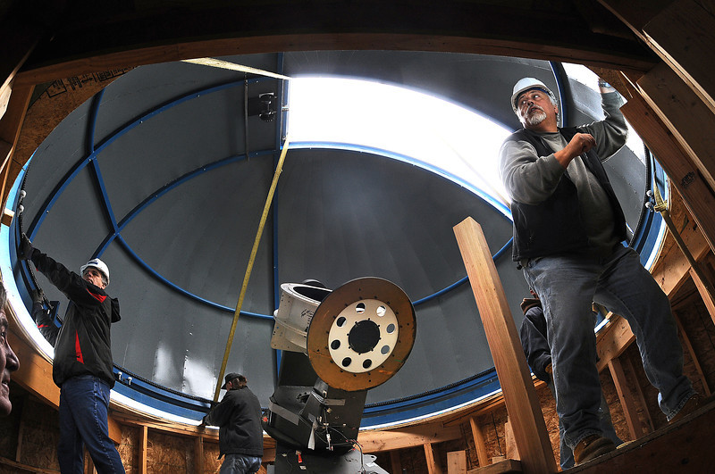 Meinte Veldhuis, president of the Little Thompson Science Foundation, right, settles an observatory dome atop the East Pier Room of the Little Thompson Observatory in Berthoud with the help of observatory boardmember Mark Rennert, left, observatory cofounder Tom Patterson, background, and Matt Barnhardt of Quality Fabricators, behind Veldhuis. The telescope is intended to fully robotic so it can be accessed remotely by users around the world.