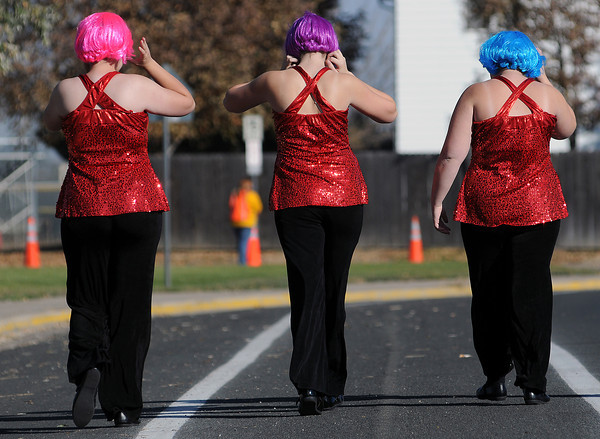 From left, Makenzie Wilson, 17, Lindsi Durrett, 15, and Anna Schafman, 17, of Estes Park High School walk down Eagle Drive before they perform at the Northern Regional Band Competition at Thompson Valley High School on Wednesday.
