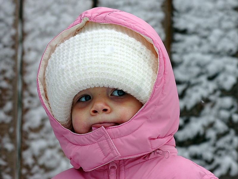 All bundled up staying warm in the snow, Peyton Olson, 18 months, watches neighborhood children play in the snow on the 1100 block of West Sixth Avenue in Loveland on Thursday.
