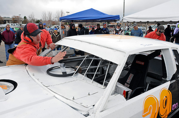 Kevin Hiner of Fort Collins, left, and Jimmy Dyer of Greeley rush to change tires, wipe windows and fuel up a race car as they comptete in the pit crew challenge during the Race Car Show on Sunday at Orchards Shopping Center.