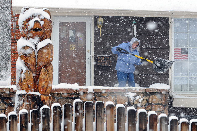 Dorothy Armstrong shovels the porch at the home that she shares with her sister Sarah Maxine Griffith on Eighth Street. A snow storm moved in Tuesday morning and forecasters expect it to continue through this evening.