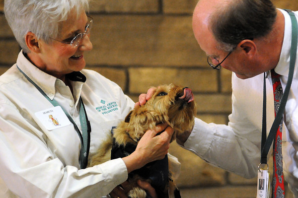 Medical Center of the Rockies Chaplain Donald Orwick, right, blesses a Norwich terrier named Tucker owned buy Marcia Oliphant, left, of Windsor at the Blessing of the Paws event at the hospital. Tucker and other members of the MCR Volunteer Pet Therapy Team were honored Sunday for the work they do at the hospital.