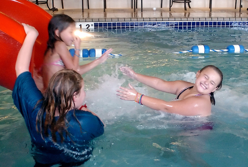 Reagan Faughnan, 10, left, looks on while Cecilia Velarde, 7, zips down a water slide in front of Haley Wade on Saturday at Holiday Inn Express during a pool party celebrating Haley's tenth birthday. Haley turned ten years old on Sunday, when the date was 10/10/10.