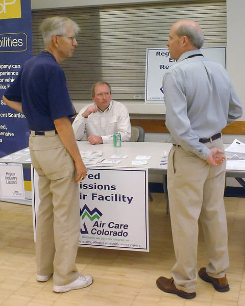 Loveland resident Steve Venzke, left, has his questions about emissions testing answered by Bill Haan, back, of Air Care Colorado, and Jim Kemper of the Colorado Department of Public Health and Environment during an open house Saturday at the Chilson Senior Center to present information about the planned resumption of emissions testing in Larimer County.