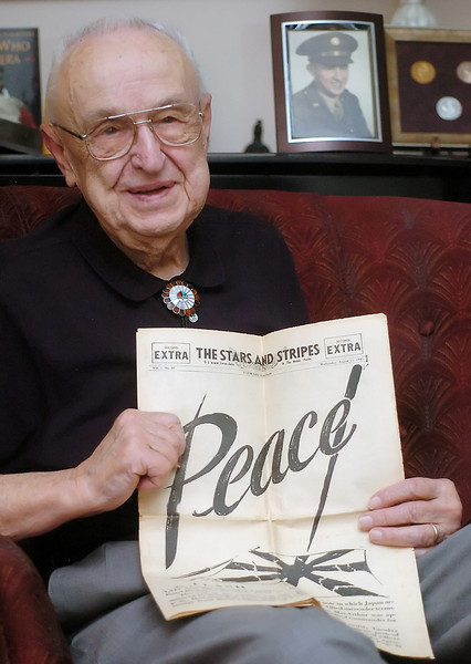 World War II veteran Hudson Grotzinger holds his copy of The Stars and Stripes newspaper that was published Aug. 15, 1945, the day after the war with Japan ended.