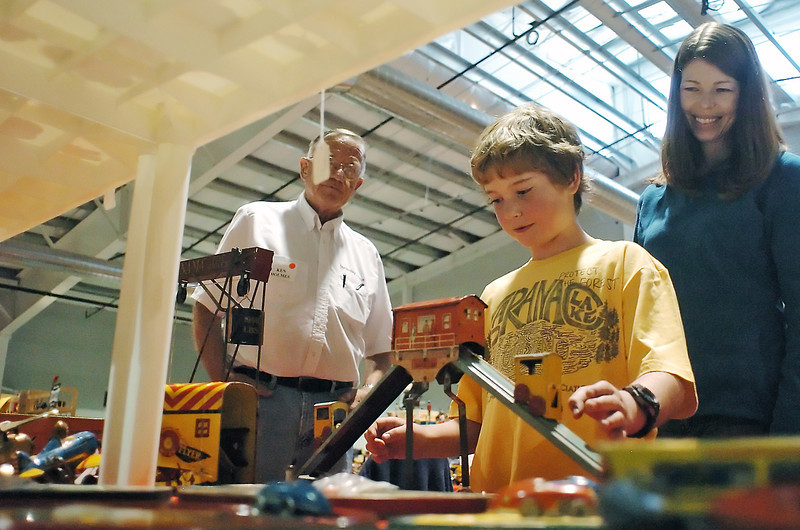 Wichita, Kan. resident Ken Holmes, left, assists 8-year-old Noah Hollingsworth and his mother, Brandi, of Fort Collins, as they look at an antique toy on display at Holmes' booth during the Timber Dan Antique and Collectible Toy Show on Saturday at The Ranch.