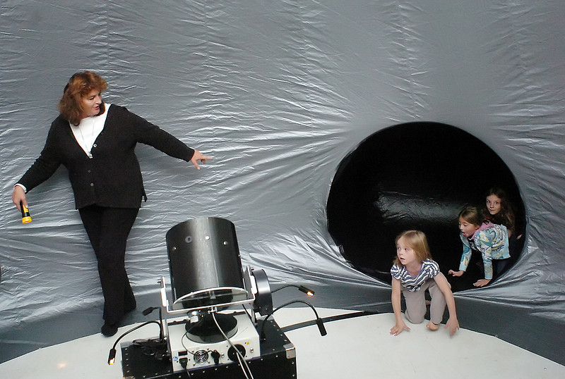 Thompson School District Science Coordinator Jan Lanting, left, leads Courtney Dumont, 5, Brooke Dumont, 7, and Sofia Doyle, 8, into the Starlab portable inflatable planetarium during the Space Night event at Van Buren Elementary School on Wednesday, Oct. 27, 2010. Once the Starlab was filled with students and their parents Lanting turned out the lights and projected pictures of the stars and planets onto the walls.