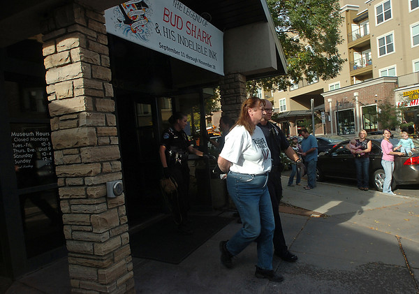 Kathleen Folden of Kalispell, Mont., is lead out of the Loveland Museum/Gallery in handcuffs Wednesday, October 6, 2010, after she allegedly smashed Plexiglass with a crowbar and tore up part of a controversial piece of art. (AP Photo/Loveland Reporter-Herald, Jenny Sparks)