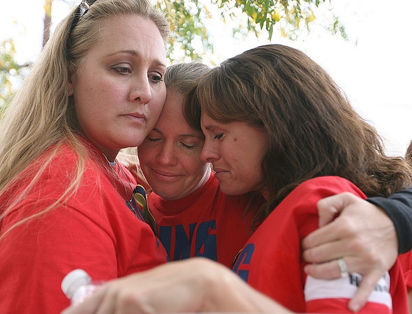 From left, Nikki Hartley, David's sister, Melanie Hood, and Stephanie Thoen, both cousins of David, hug during a protest Friday at the Mexican Consulate in Denver. Photo by Gabriel Christus)