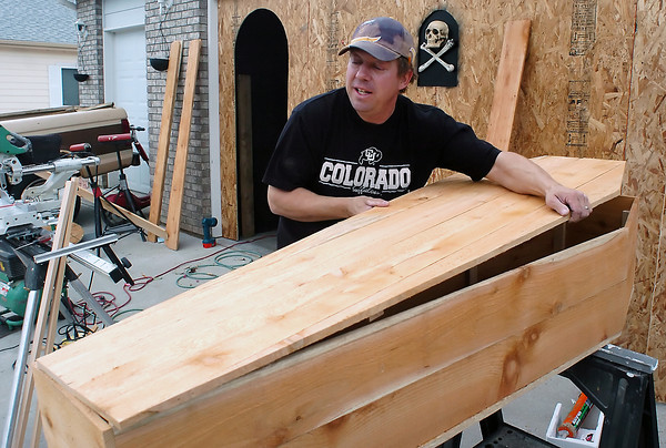 Doug Schmidt constructs a prop coffin known as a toe-pincher on Friday outside his home in northwest Loveland. Schmidt enjoys building decorative coffins and a variety of other props for the Halloween holiday.