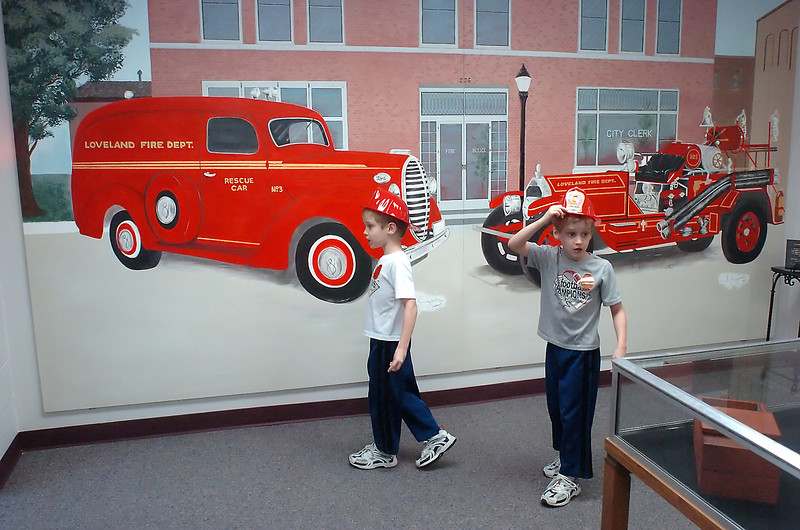 David Udlock, 5, left, and his twin brother, Joshua, walk past the new mural in the Loveland Fire Exhibit located in the Loveland Museum/Gallery Sequel while attending an open house there on Saturday.