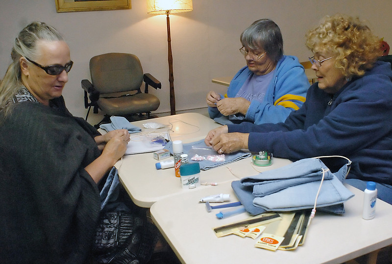 Volunteers at the Loveland Odd Fellows Lodge, from left, Linda Benefiel, Joan Schreiber and Linda Marshall, assemble and fill denim bags with toiletry items on Tuesday night that will be distributed to homeless individuals in Loveland. The bags contain a variety of items including a toothbrush, toothpaste, comb, shampoo, deoderant, shaving cream, disposable razor, bar soap, mouthwash and socks.