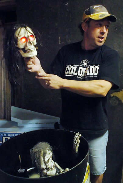 Doug Schmidt demonstrates the red, glowing eyes of a prop skull he modified to be used as a Halloween decoration.