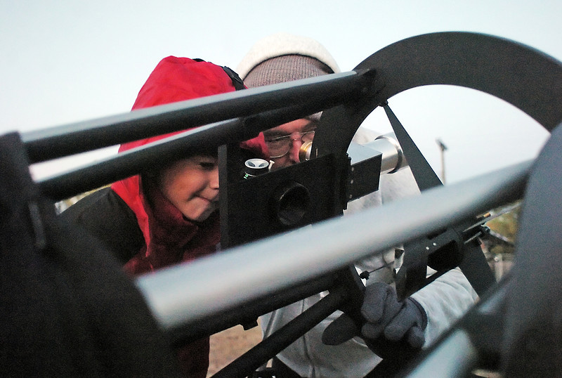 Six-year-old Matteo Scalise, left, looks through a reflecting telescope at the planet Jupieter with the assistance of Jon Caldwell on Tuesday outside Van Buren Elementary School during Space Night. Members of the Northern Colorado Astronomical Society set up several telescopes for visitors to the event to learn about the stars and planets.