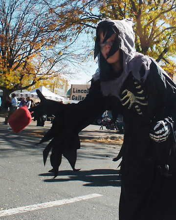 Dressed as the Grim Reaper, 8-year-old Jesse McGarvey Jr. tosses a bean bag at a target while playing a game during the Halloween Family Fun Festival in downtown Loveland.