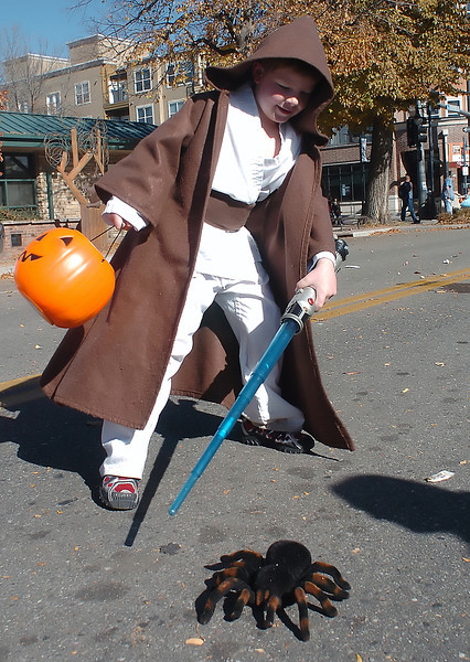 Six-year-old Evan McMaine fends off a remote-controlled spider with his light saber while dressed as ObiWan Kenobi during the Halloween Family Fun Festival on Saturday in downtown Loveland.