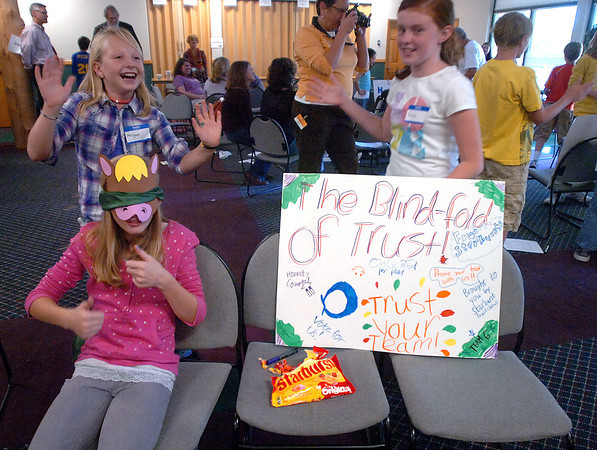 Sara Kady, 10, bottom left, sports a horse mask and a blind fold as her team mates Morgan Simmonds, 10, left, and Emma Blundell, 10, right, try to market a product they created during the Young Writers Fun Shop hosted by Group Publishing in Loveland on Thursday. Fifth graders experienced hnads-on publishing in a real work environment. They focused on an activity that could be used to teach a lesson and learned about marketing, accounting, editing, design and more.