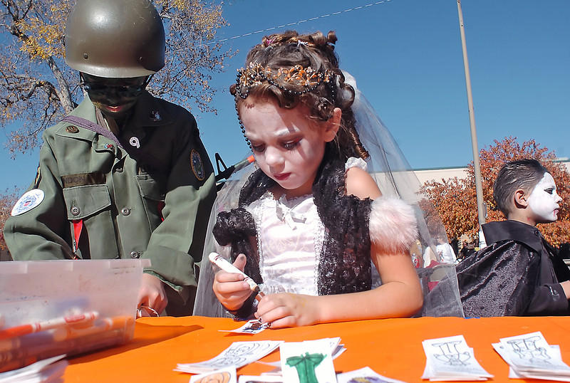 Wesley Palmer, 12, left, dressed as G.I. Joe and Taylor Apodaca, 9, as Bridezilla, color bookmarkers Saturday at the Loveland Museum/Gallery's booth during the Haloween Family Fun Festival in downtown Loveland.