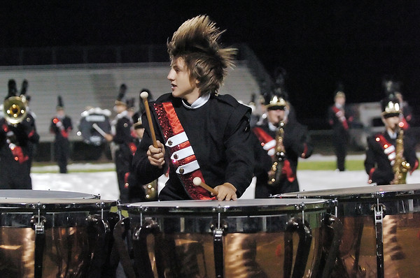 Loveland High School freshman Mikey Veit's hair goes flying while he plays timpani with the school's Crimson Regiment marching band Wednesday night at Patterson Stadium during the Colorado Bandmasters Association Northern Region State Qualifying Event.