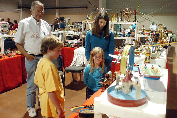Yesterday's Toys owner Ken Holmes, left, of Wichita, Kans., assists Fort Collins residents Noah Hollingsworth, 8, Chloe Hollingsworth, 7, and Brandi Hollingsworth as they look at toys on display at Holmes' booth on Saturday during the Timber Dan Antique and Collectible Toy Show at The Ranch.
