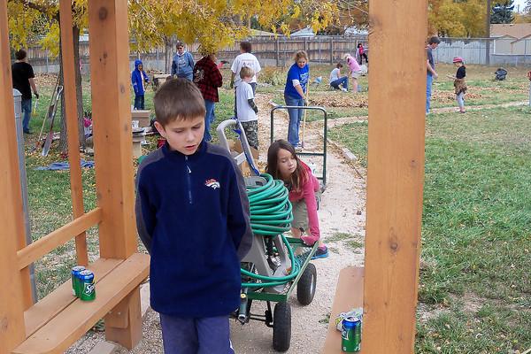 Fifth-grader Michael Wangler, 10, hauls away a hose system earlier this month from the School/Neighborhood Garden at Van Buren Elementary.