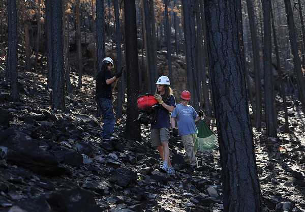 Tully Henke, 15, center, spreads seed on land that was burned in the High Park fire as classmates David Gonzalez, 15, left, and Sam Cluett, 15, right, use rakes to cover the seed Tuesday in the Redstone Canyon. Land owner Mark DeGregorio, who lost his home in the fire, allowed biology students from the Polaris Expiditionary Learning School to reseed on his property as a learning experience. Students will monitor the progress through the years.