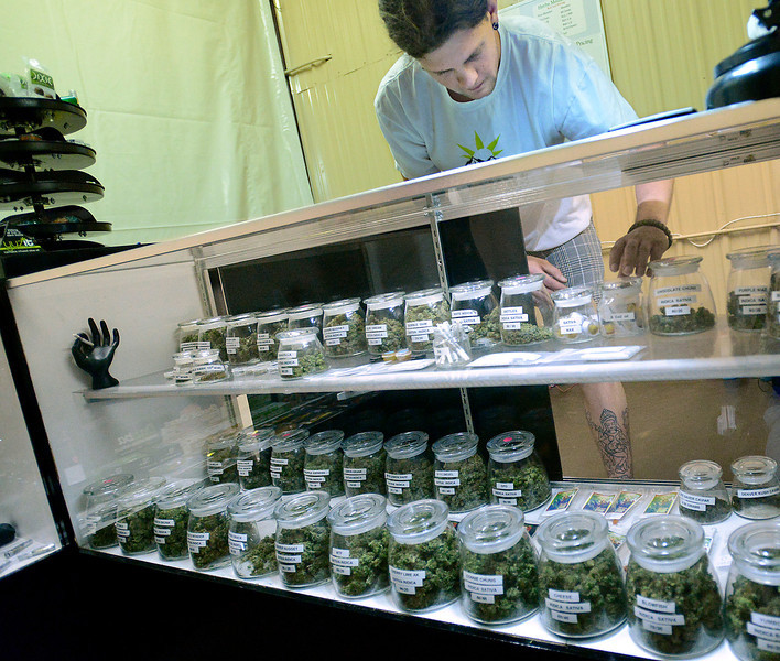 Justin Bartkowski, an employee at Herb's Medicinals, a medical marijuana dispensary in Berthoud, arranges different kinds of medical marijuana recently after moving into  the dispensary's new location in Berthoud.