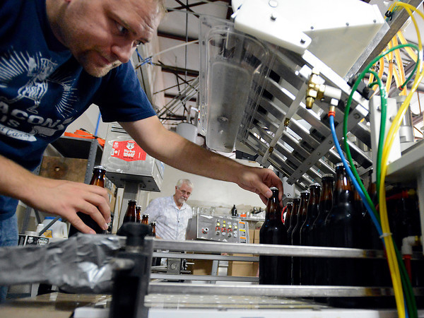 Myles Howard, left, moves bottles of Grimm Brothers beer onto the conveyor belt as Don Chapman Snr, center, puts the beer in boxes after a label is attached Wednesday in Loveland while bottling beer in a warehouse near the Grimm Brothers Brewhouse.
