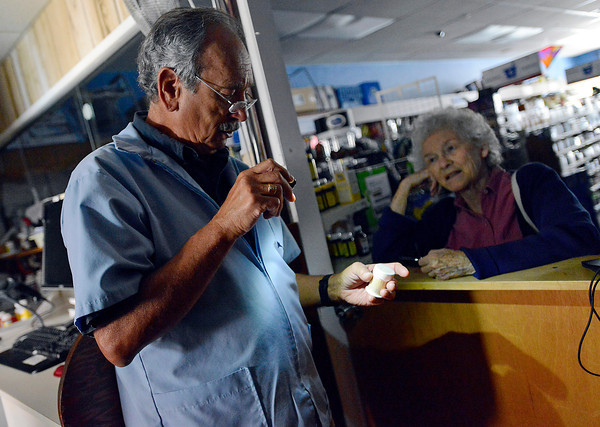 Pharmasist Fred Bruno, left, uses a flashlight to look at a product for customer Barbara Van Kleek Tuesday in a dark Berthoud Drug during a power outage.