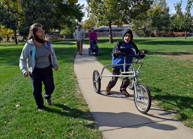 Logan Sweezy, 13, smiles as shows his grandmother Kathy Friesen, left, how fast he can go on his bike Friday morning at Silver Glen Park in Loveland. His mom Eadie Sweezy, back right, and new friend Matt Kaufman, back left, aslo watch him ride. Kaufman specially designed and built the bike for Logan, who has cerebral palsy.
