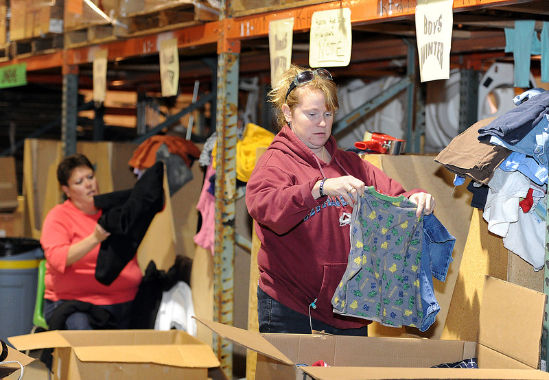 Volunteers Stacie Elmore, front, and Lee Ann Ohmie sort through donated clothing Monday at the H.E.L.P. International warehouse in Loveland. The service organization is prepared to help with relief from Hurricane Sandy if needed and they have a truck and trailer ready to move supplies.