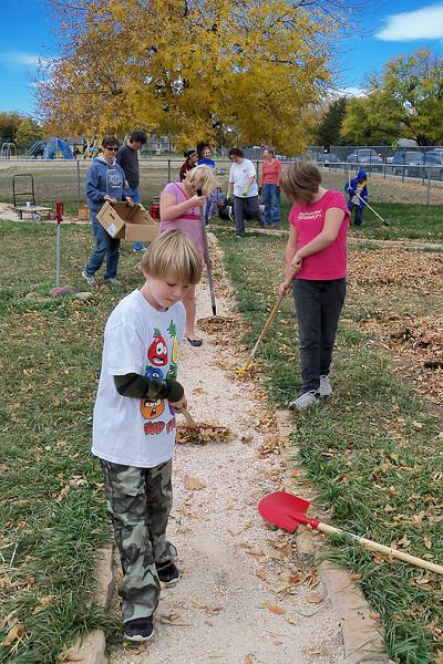 Third-grader Jacob Gargan, 8, and members of the Van Buren community rake up leaves earlier this month from the school and neighborhood garden.
