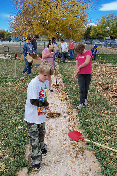 Third-grader Jacob Gargan, 8, and members of the Van Buren community rake up leaves earlier this month from the school and neighborhood garden.