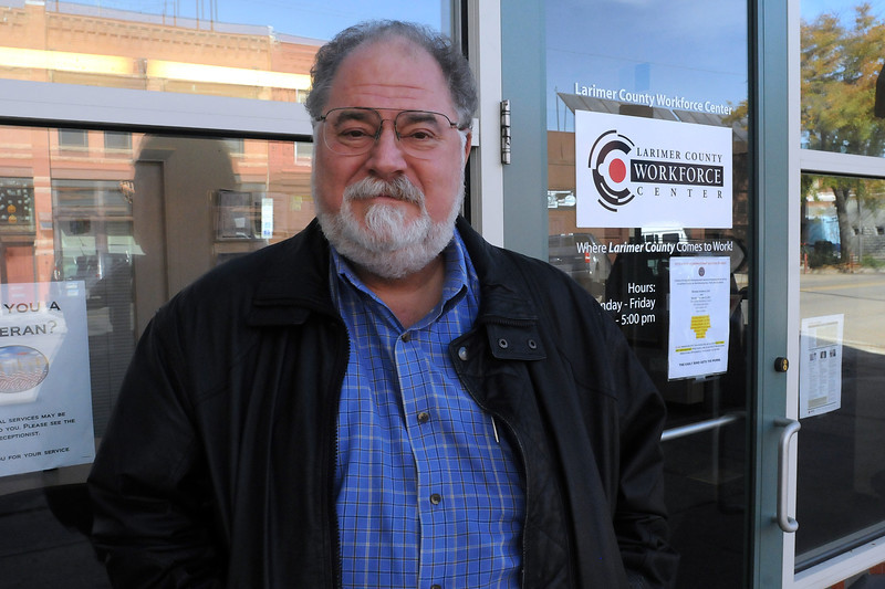 Lew Wymisner, assistant director of the Larimer County Workforce Center, stands in front of the agency's Loveland office, 418 E. Fourth St. Wymisner is retiring this week after 34 years on the job. (Photo by Craig Young)