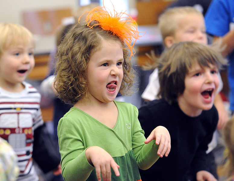 "Finley Crockett of Loveland, 3, makes a silly face as she dances to the ""Silly Dance Contest"" song with other kids Wednesday during story time at the Loveland Public Library."