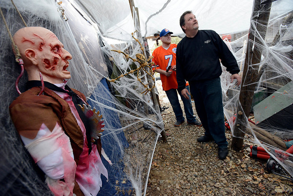 Scott Hood, right, and his son Matthew Hood look over the spooky mine shaft area Monday they created in the backyard of their Loveland home for trick-or-treaters. They are transforming their garage, backyard, and part of their home into a haunted house with different creepy themes.